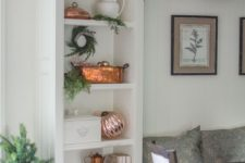 13 a built-in shelf styled for Christmas with rose gold ornaments and copper touches plus evergreens is a very chic idea