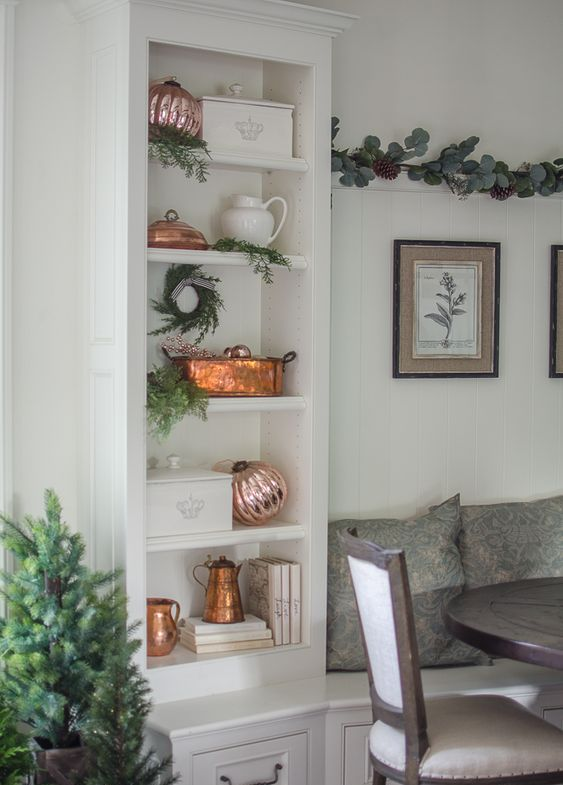 a built-in shelf styled for Christmas with rose gold ornaments and copper touches plus evergreens is a very chic idea