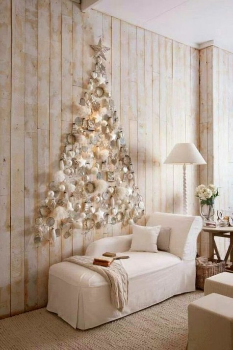 a creamy and mother of pearl wall-mounted Christmas tree with ornaments of various sizes and shapes
