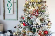 13 a flocked Christmas tree decorated with plaid ornaments and ribbons, lights, snowflakes and metallic touches