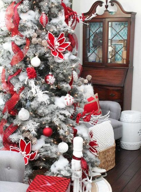 a flocked Christmas tree decorated with plaid ribbons, fabric blooms, white ornaments and other decor