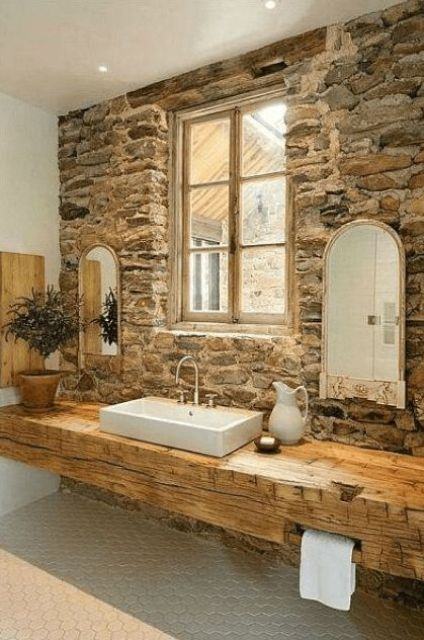 a rustic bathroom with a stone accent wall, a rough wooden slab vanity and some greenery and mirrors