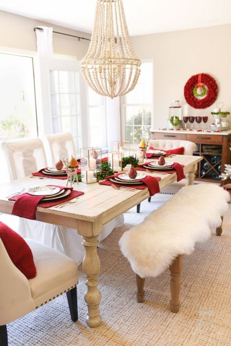 a chic Christmas dining room with burgundy napkins and pillows, touches of white fur and candles