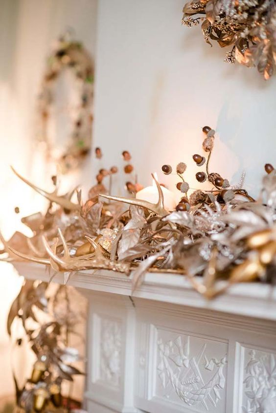 a copper and gold Christmas mantel with acorns, berries, antlers, leaves and garlands looks very festive and bold