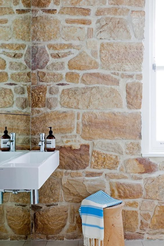 a rustic chic bathroom with a rough stone wall with neutral grout and a wooden stool that are an amazing combo