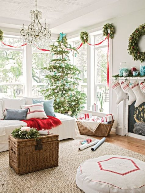 a cozy Christmas living room with evergreen wreaths and a Christmas tree, red ribbons, blankets and touches