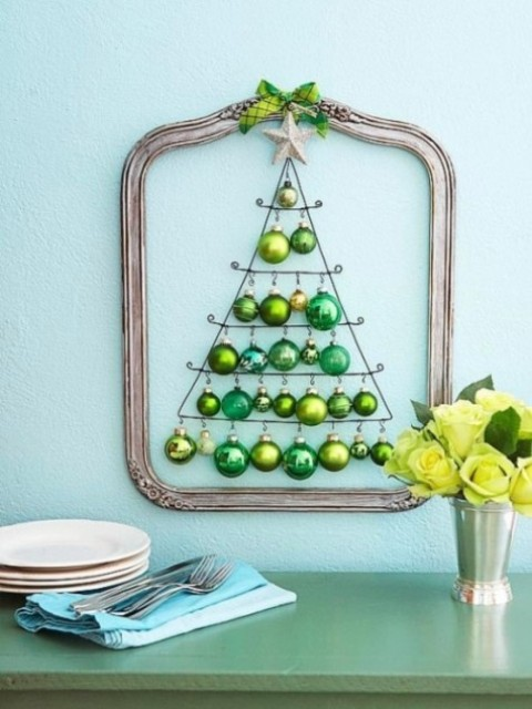a framed wall-mounted Christmas tree of green ornaments of various shades looks very holiday-like