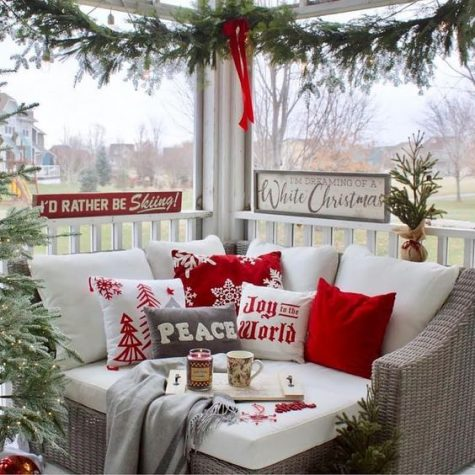 a cozy Christmas nook on the porch with red and white pillows, an evergreen garland and signs and candles