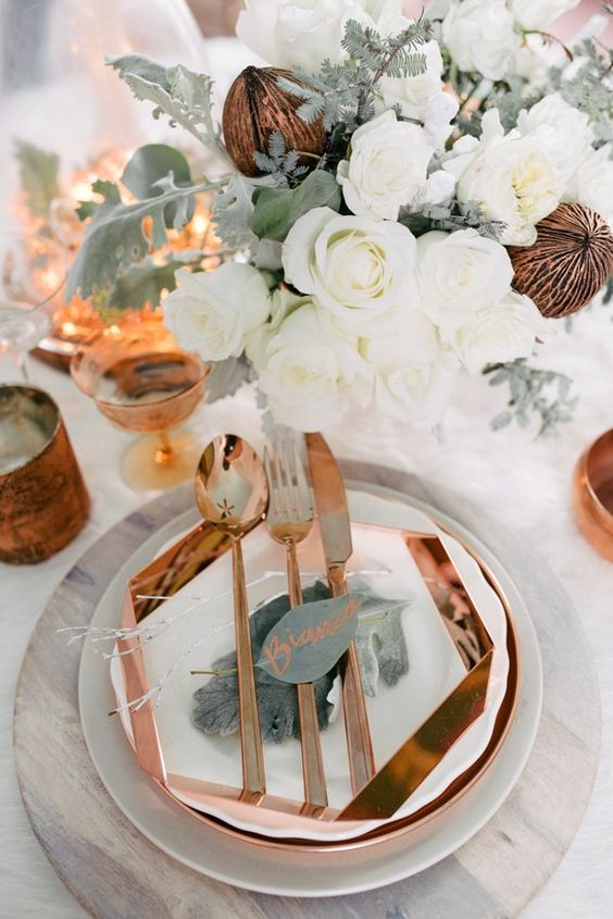 a geometric copper charger and cutlery look very elegant paired with white blooms and plates plus amber glasses