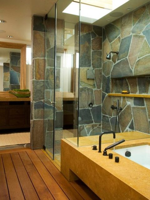 a contemporary bathroom with a touch of rustic chic – a stone wall and stained wooden floors