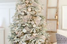 17 a flocked Christmas tree with lights, metallic ornaments, snowflakes and shiny mesh ribbons looks festive