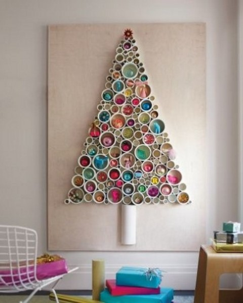 a PVC pipe Christmas tree with various ornaments and toys inside is a cool idea for a bright modern space