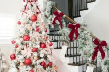 18 a flocked Christmas tree with red and metallic ornaments, pink fabric flowers and lights is a modern take on a traditional one