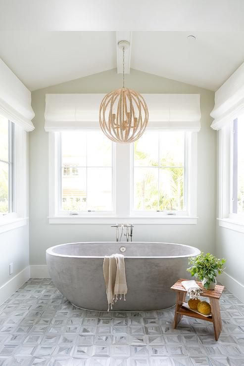 a light-filled vintage bathroom with a pendant lamp, a sleek stone bathtub and printed grey tiles on the floor