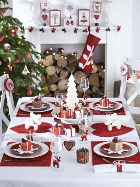 a modern red and white Christmas table setting, red and white ornaments and stockings and a tree decorated in the same colors