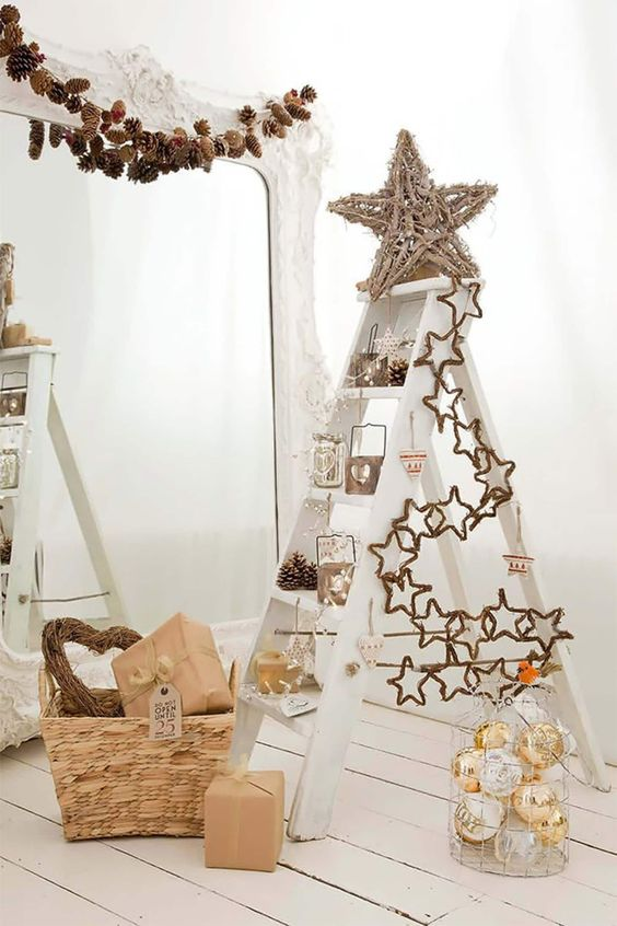 a ladder used as a Christmas tree, with twine stars and sticks, with lights, pinecones, ornaments and frames