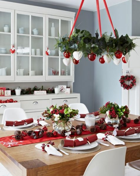 a red and white Christmas chandelier, a red table runner and berries for decorating a dining zone in a festive way