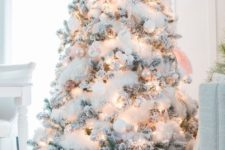 20 a flocked Christmas tree with white and pastel ornaments, lights and fluffy cotton garlands looks fairy-tale-like
