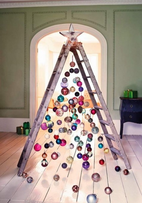 a ladder with ornaments hanging from it looks colorful and industrial and is a whimsical decor idea