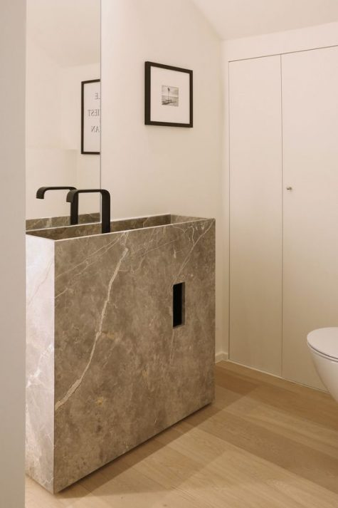 a minimalist sink and vanity of stone with a matte black faucet for a tiny powder room