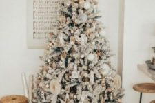 21 a magical flocked Christmas tree with white balls, whimsy and shiny ornaments, bells and little house ornaments