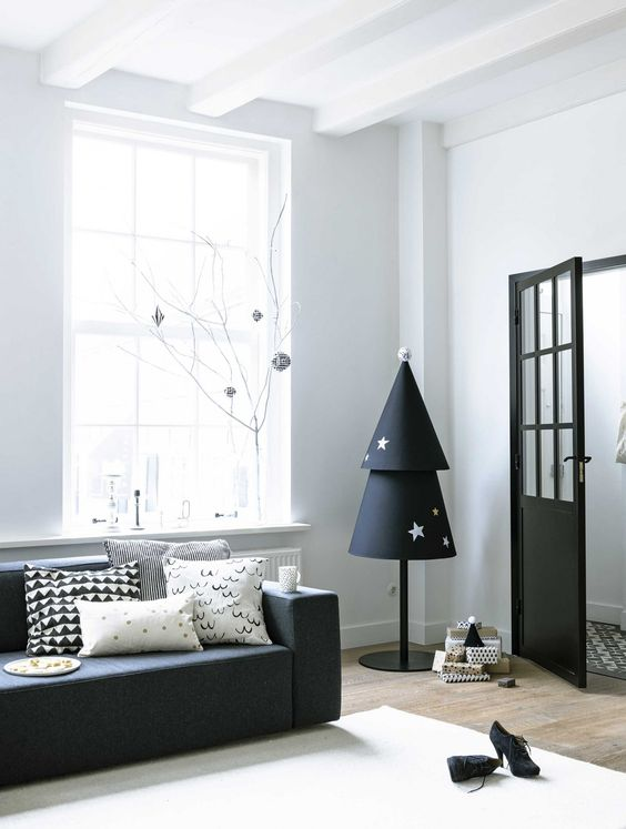 a paper Christmas tree in black and white with stars on a pole is a cool idea for a monochromatic or minimalist interior