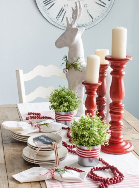 a simple red and white Christmas tablescape with candles, fresh greenery and cranberries in a garland