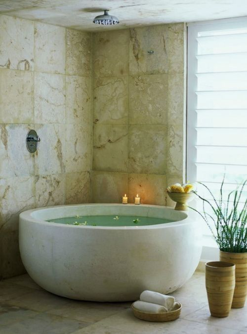 a spiritual bathroom nook done with stone-like tiles and a sleek stone round bathtub