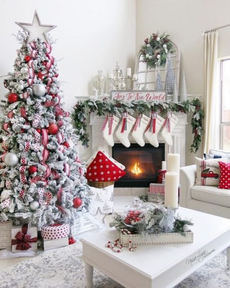 a super cozy and chic farmhouse space done in red and white for Christmas – with a flocked tree, stockings, printed pillows and wreaths
