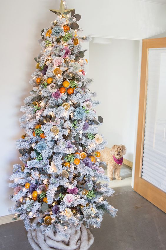 a whimsical flocked Christmas tree decorated with flowers and citrus and citrus slices plus lights