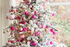 23 bold fuchsia and gold ornaments stand out on a flocked Christmas tree and add a bright and colorful touch to the space
