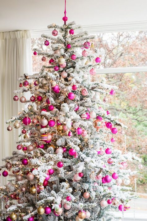 bold fuchsia and gold ornaments stand out on a flocked Christmas tree and add a bright and colorful touch to the space