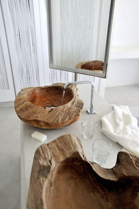 natural and rough stone sinks paired with sleek and elegant furniture look very contrasting and bold