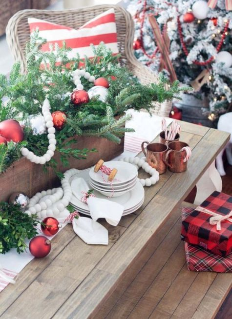 stylish Christmas decor with red, white and silver ornaments, plaid gift boxes and a striped pillow