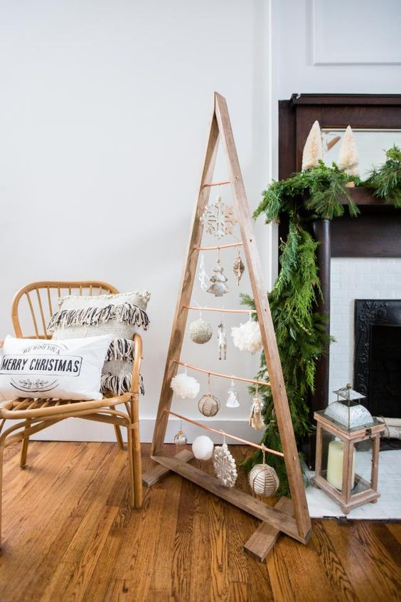 a wooden frame Christmas tree with white and silver ornaments hanging inside is a cool and cozy idea