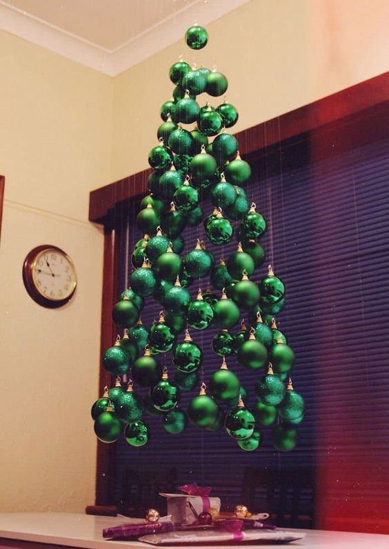 an arrangement of green ornaments hanging down to form a tree is a very bold idea
