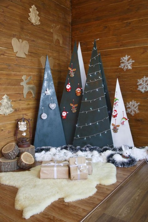 plywood cone and triangle Christmas trees with ornaments and lights on them is a stylish idea with a modern feel