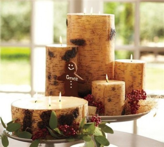 a Christmas centerpiece  of candles wrapped with birch bark, greenery and berries is easy to DIY