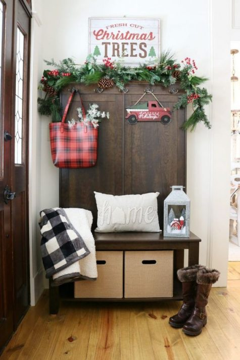 a Christmas sign, an evergreen garland with pinecones and berries, plaid decor and a lantern