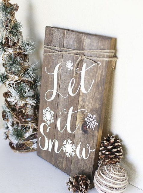 a Christmas sign of a wooden plaque, with snowy pinecones and a mini Christmas tree next to it
