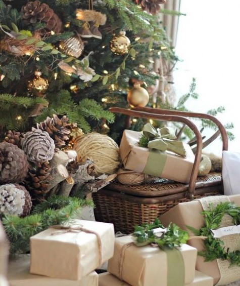 a Christmas tree with greenery, gold ornaments and pinecones, firewood, pinecones and yarn balls and a basket with gifts