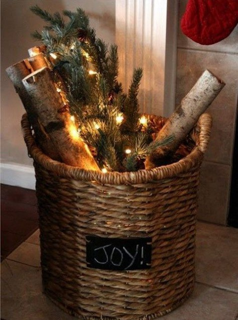a basket with evergreens, firewood and lights can act as a Christmas decoration itself
