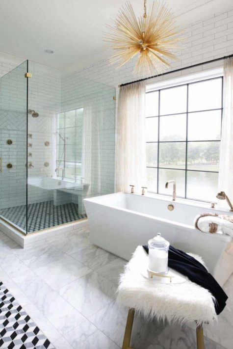 a beautiful eclectic space with a catchy tub, a sunburst chandelier, a faux fur stool and mosaic tiles