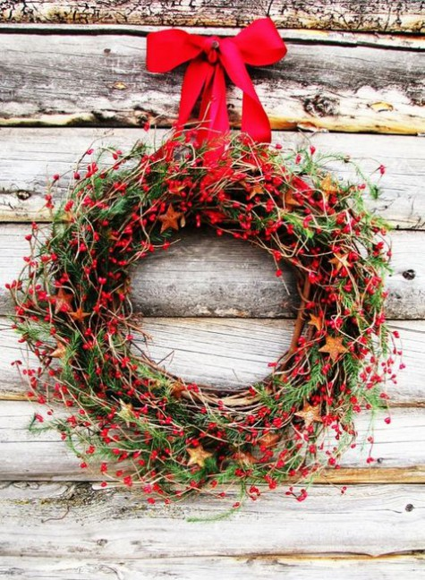a bold rustic Christmas wreath with stars cut of ornages, lots of berries, greenery and evergreens