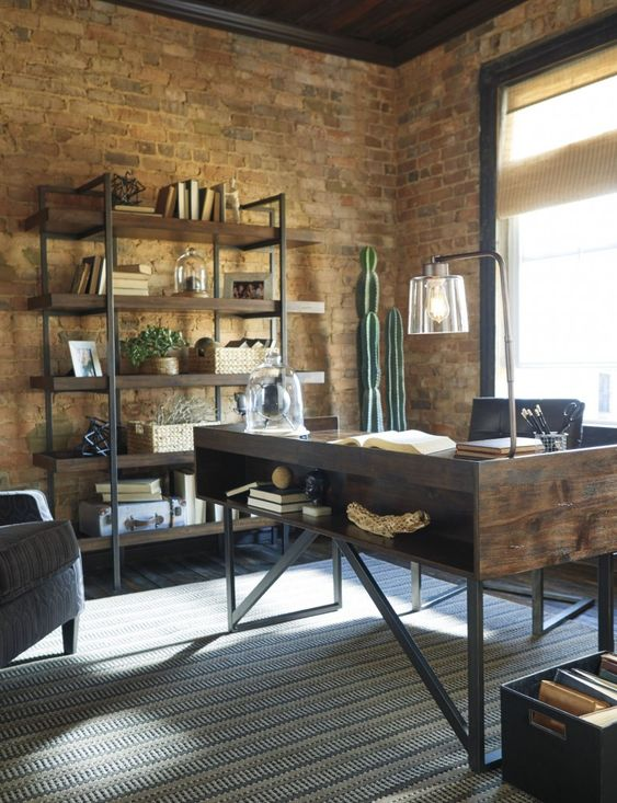 a cool industrial home office with a wooden and metal desk with storage, a large shelving uni, cacti in a pot and stylish furniture