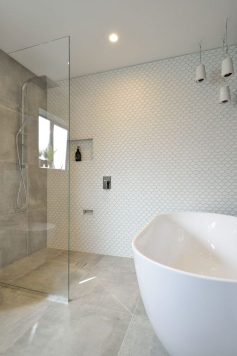 a cool small bathroom with fish scale tiles on the wall, stone grey ones, a tub and pendant lamps