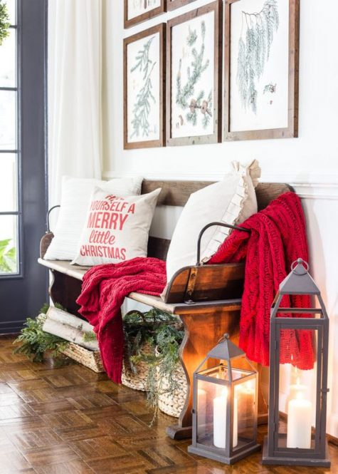 a cozy Christmas entryway with a red blanket, some cute pillows, baskets with evergreens and firewood, candle lanterns