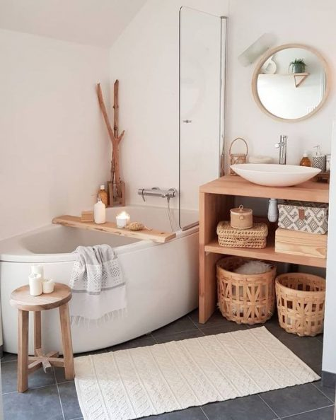 a cozy neutral bathroom with a free-standing tub, a wooden vanity and baskets and branches