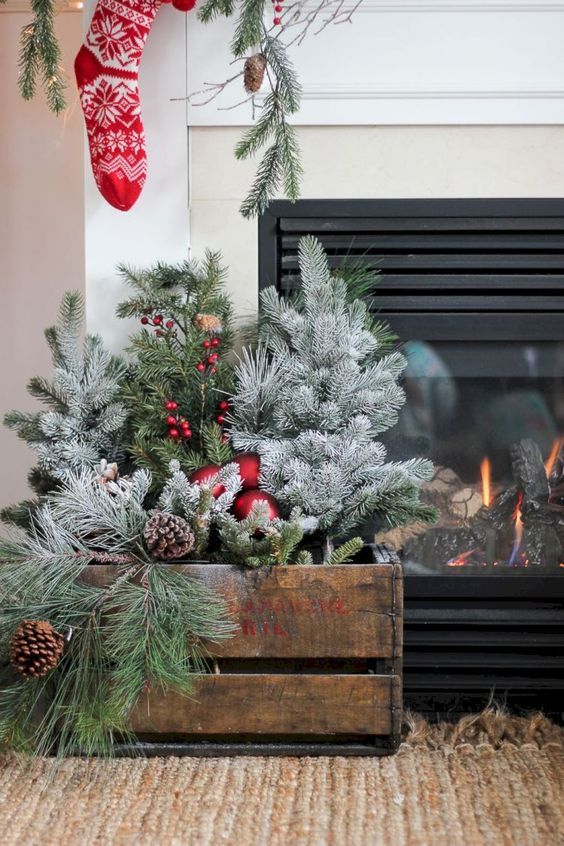 a crate with evergreens, red ornaments, pinecones and berries is a cool Christmas decoration to compose