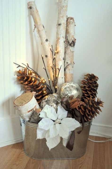 a galvanized bathtub with firewood, large pinecones, a poinsettia flower, lights and ornaments is a Christmas decoration for any space